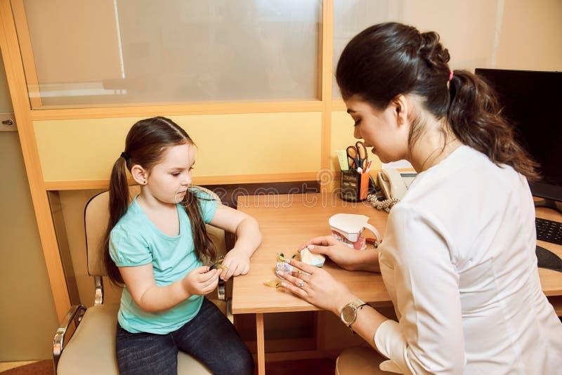 De tandarts toont een klein meisje hoe te om het gebit schoon te maken royalty-vrije stock foto's