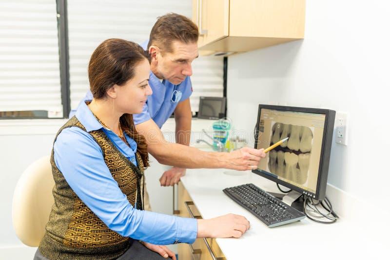 De tandarts verklaart geduldig allebei die röntgenstralen bekijken stock foto