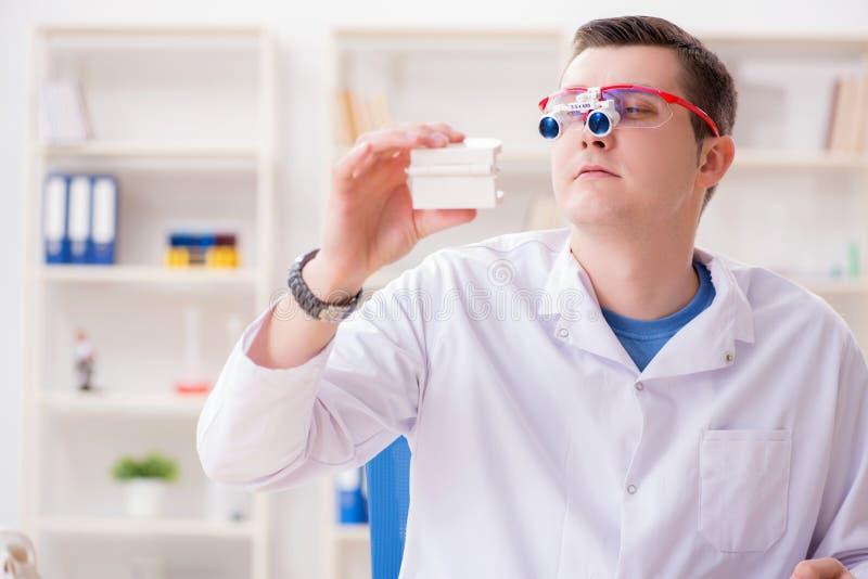 De tandarts werkende tanden inplanteren in medisch laboratorium stock fotografie