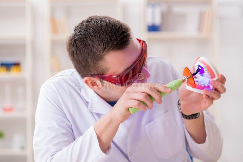 De tandarts werkende tanden inplanteren in medisch laboratorium stock foto