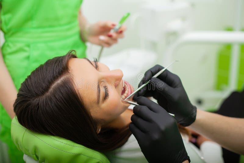 De tandartsman behandelt tanden aan cliënt in tandbureau royalty-vrije stock afbeeldingen
