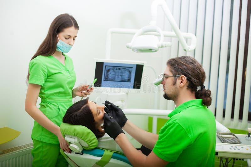 De tandartsman behandelt tanden aan cliënt in tandbureau royalty-vrije stock foto's