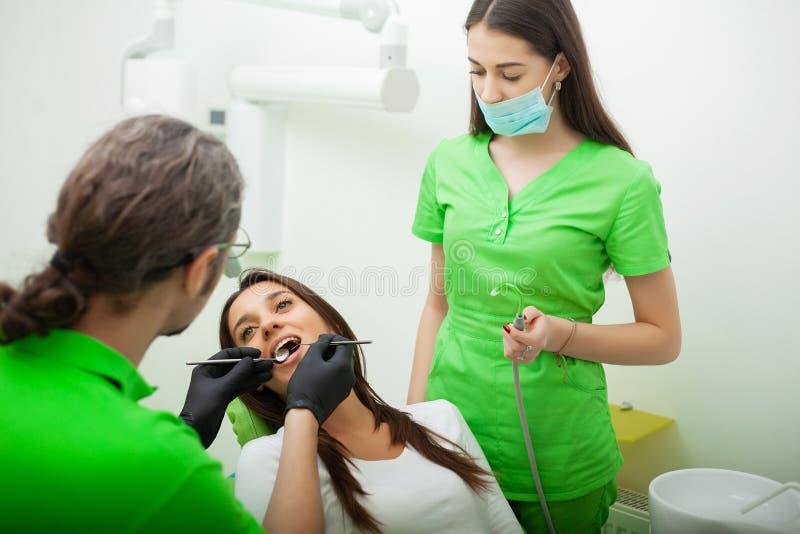 De tandartsman behandelt tanden aan cliënt in tandbureau stock fotografie