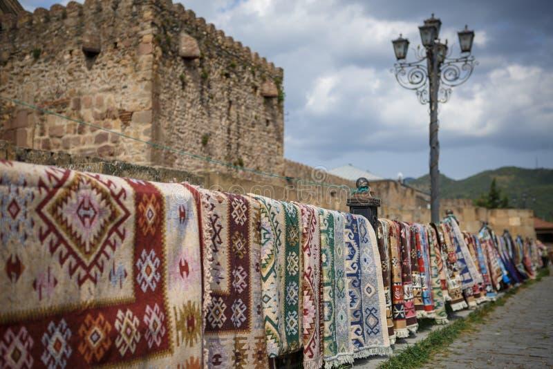 De tapijten met met de hand gemaakte ornamenten hangen op de straten van de Georgische stad voor verkoop stock fotografie