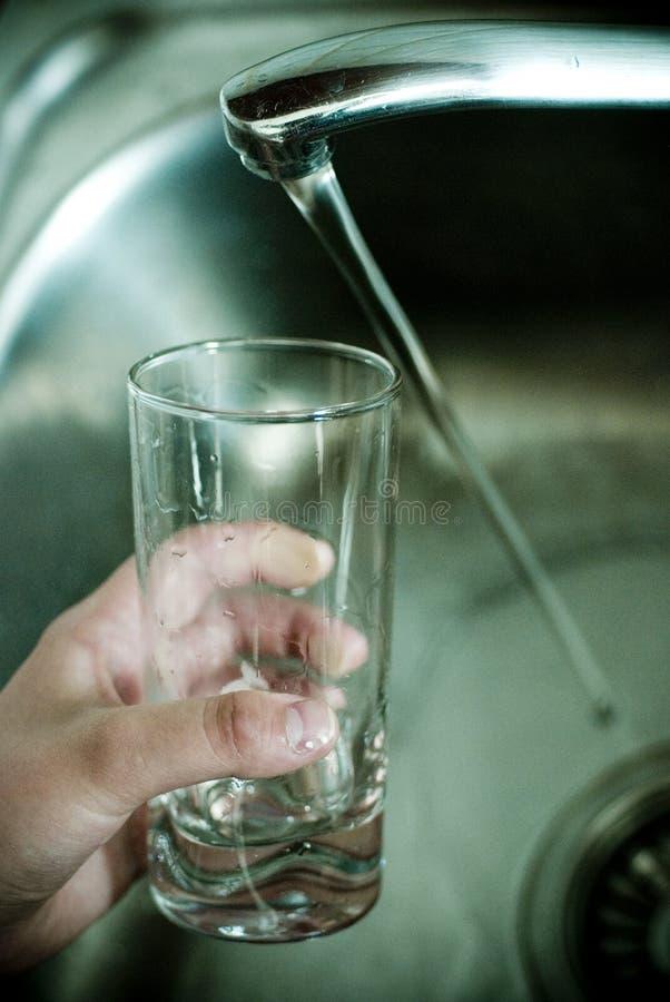 De tapkraan en het glas van het water royalty-vrije stock foto