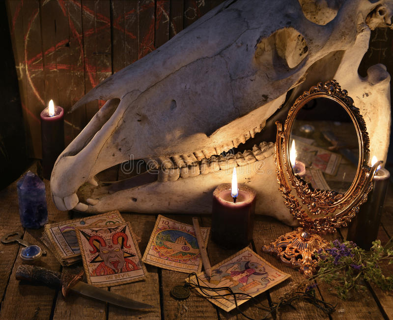 De Tarotkaarten, de magische spiegel en de paardschedel tegen de planken met pentagram stock foto
