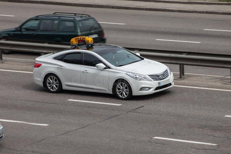 De taxi van Hyundai van de luxeauto het witte verzenden op lege weg stock fotografie