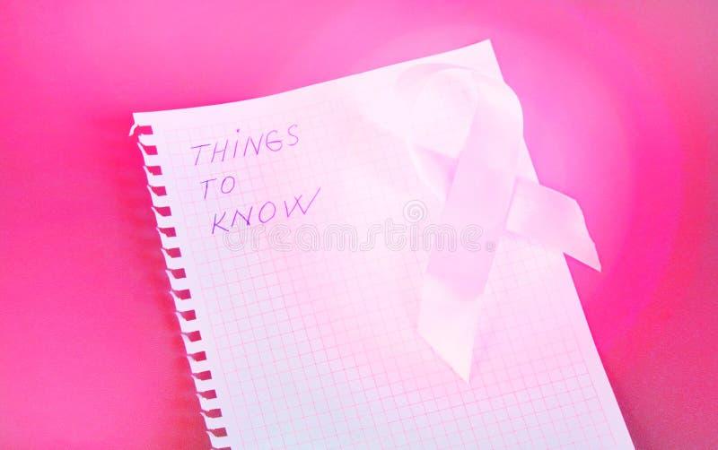 De te kennen dingen wordt geschreven in Blocnote met roze de borstkanker van de lintvoorlichting stock afbeelding