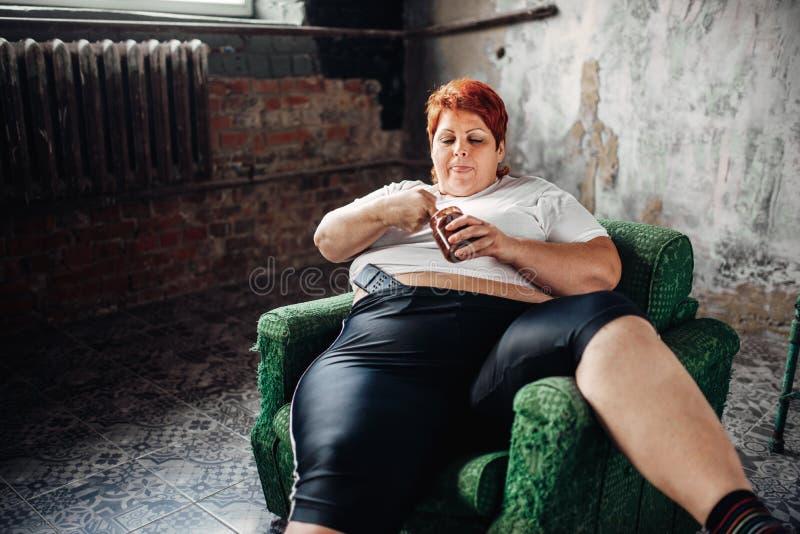 De te zware vrouw zit als voorzitter en eet snoepjes stock fotografie