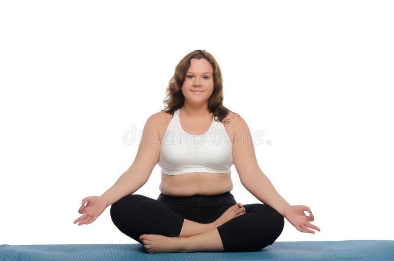 De te zware yoga van vrouwenpraktijken op mat stock afbeeldingen