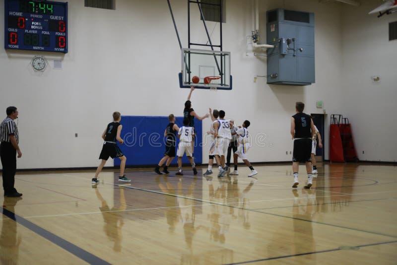De teams van het middelbare schoolbasketbal in actie stock foto
