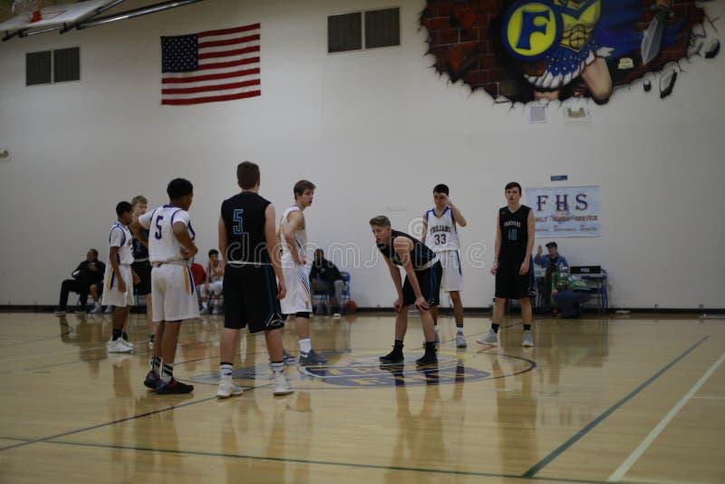 De teams van het middelbare schoolbasketbal op basketbalhof stock afbeelding