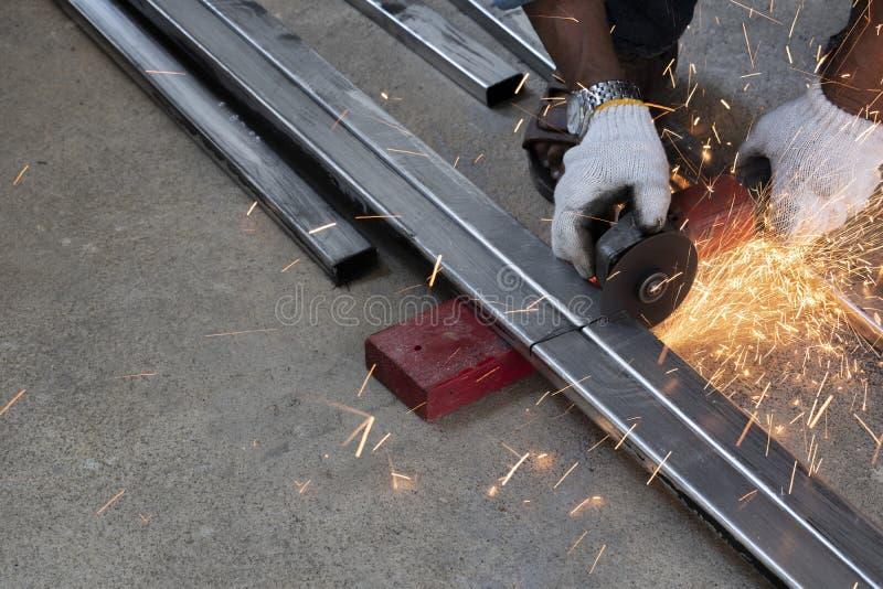 De technici gebruiken malende machines om staalpijpen te snijden stock afbeelding
