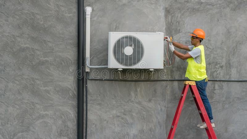 De technicus controleert airconditioner stock fotografie