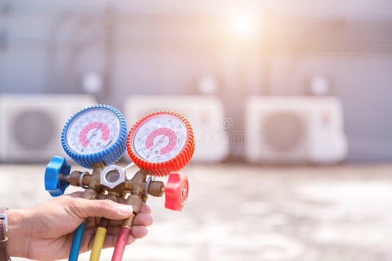 De technicus controleert airconditioner, meetapparatuur om airconditioners te vullen royalty-vrije stock afbeelding