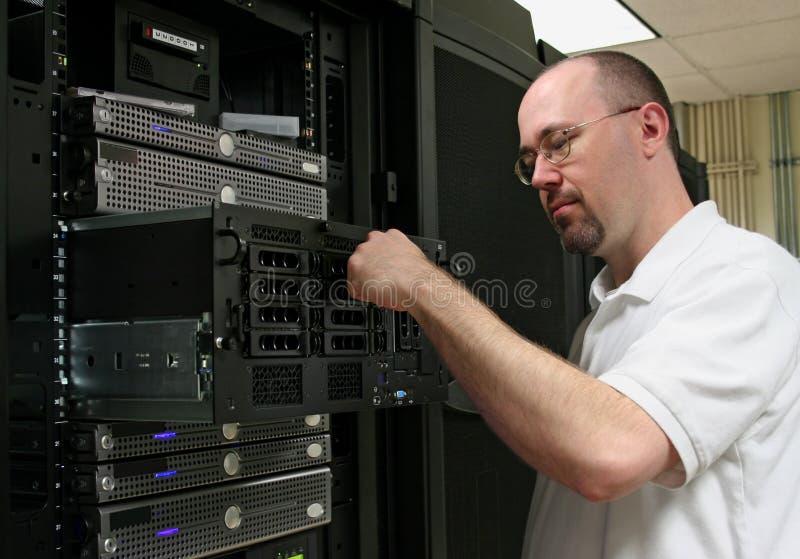 De Technicus die van de computer aan een server werkt stock fotografie