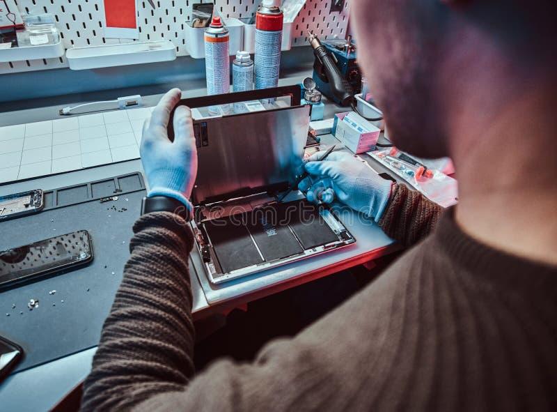 De technicus herstelt een gebroken tabletcomputer in een reparatiewerkplaats royalty-vrije stock afbeelding