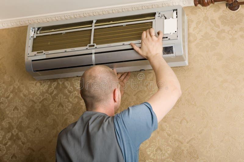 De technicus installeert een nieuwe airconditioner stock afbeelding