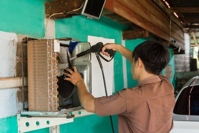 De technicus onderhoudt het herstellen en airconditioners Schone compressor met Hoge drukwasmachine royalty-vrije stock foto's