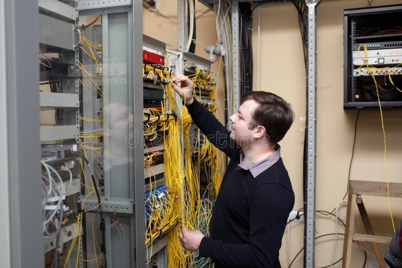 De technicus van het netwerk bij serverruimte stock afbeeldingen