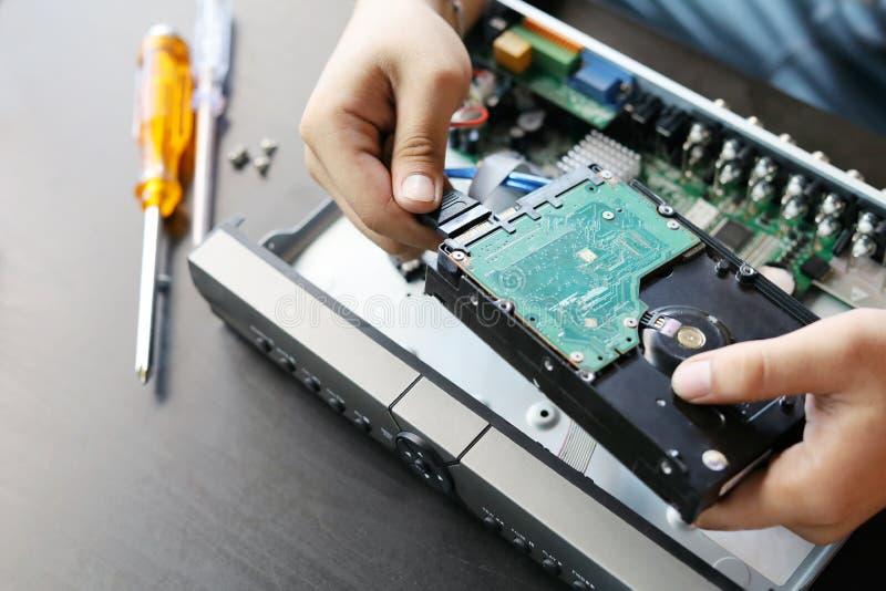 De technicus verwijdert een hardeschijfstation van het het registreertoestelgeval van kabeltelevisie DVR, om een nieuwe harde aan royalty-vrije stock fotografie