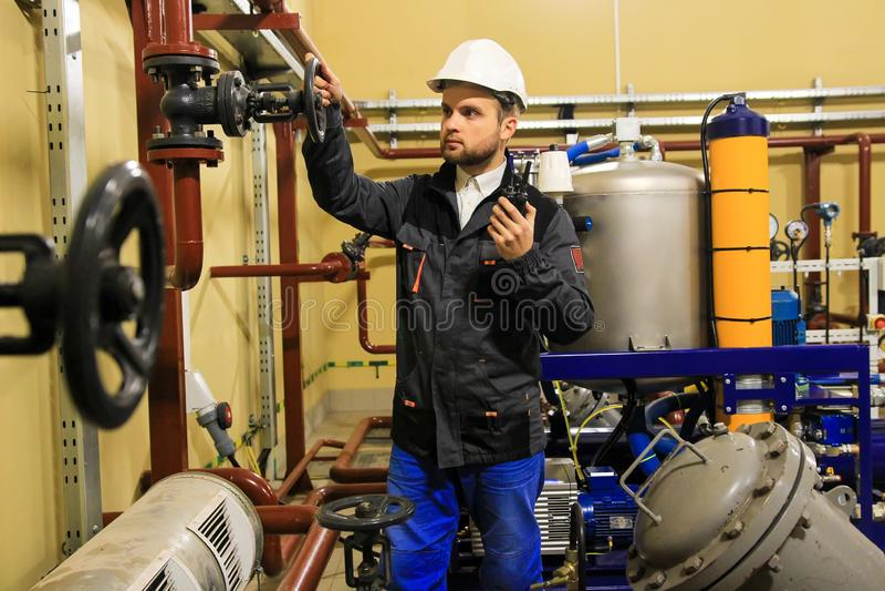 De technicusingenieur opent poortklep van pijpleiding op olieraffinaderij stock afbeelding