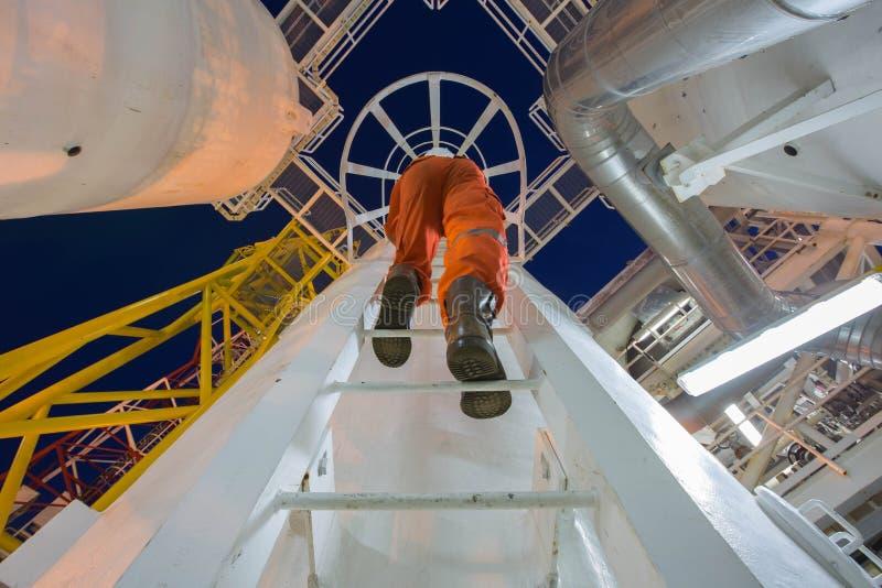 De techniek beklimt tot olie en gasprocesinstallatie aan waarnemer en inspecteert de verwerking van de gasdehydratie in nachtploe royalty-vrije stock afbeeldingen