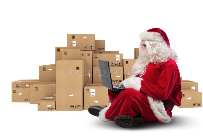 De technologische Santa Claus-zitting met laptop koopt Kerstmisgiften met e-commerce stock foto
