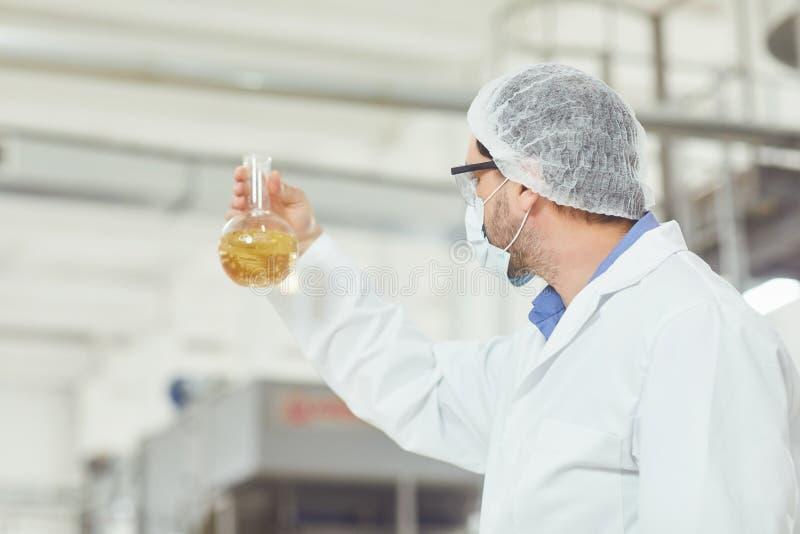 De technoloog analyseert de vloeistof in de fles op de productie stock afbeeldingen