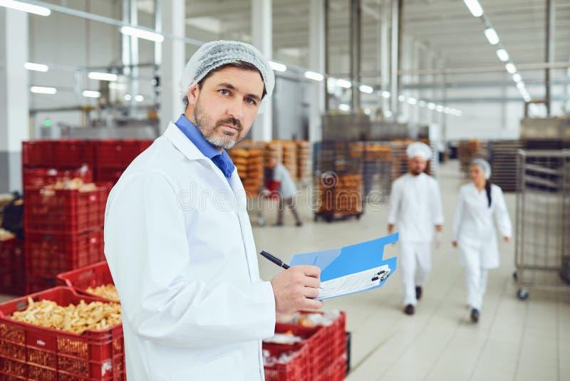 De technolooginspecteur maakt een ingang in de omslag met de documenten bij de fabriek stock foto's