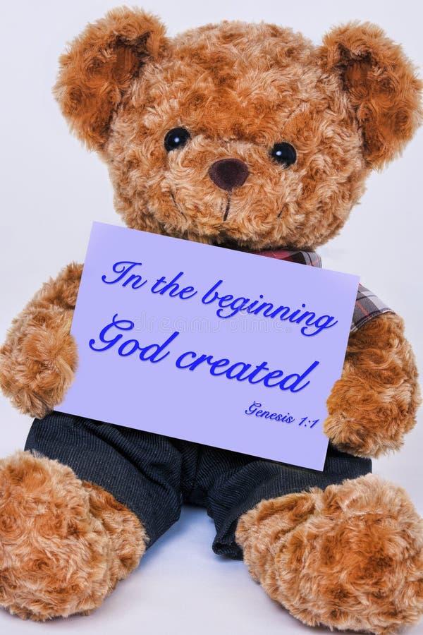 De teddybeer die een teken houden dat in het begin God zegt creeert royalty-vrije stock afbeeldingen