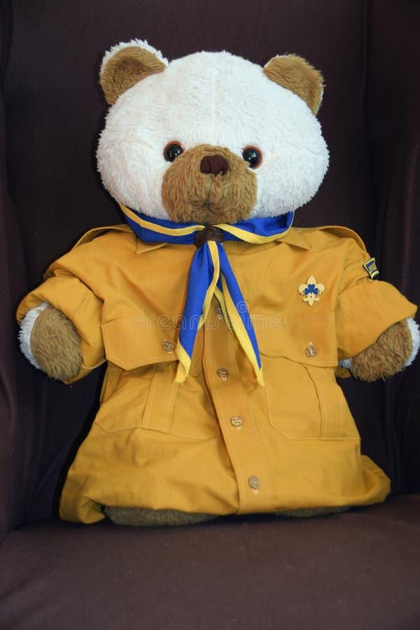 De teddybeer kleedde zich in verkennersoverhemd en sjaal op de stoel royalty-vrije stock foto's