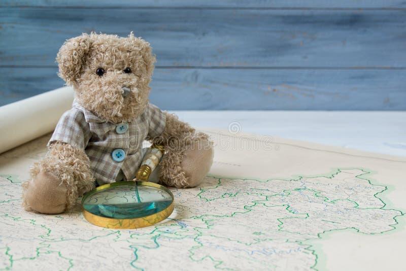 De teddybeer met antiek vergrootglas ziet de oude kaart van Duitsland stock foto's
