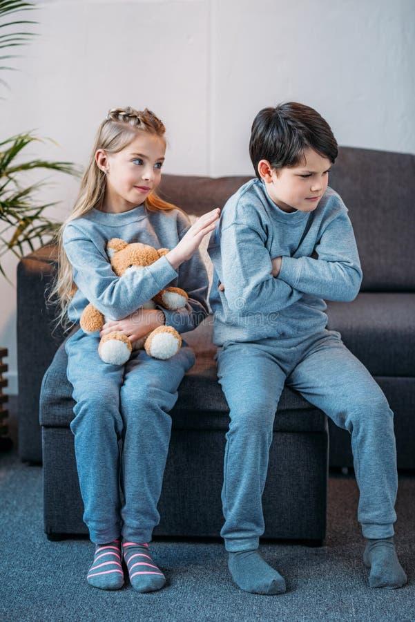 De teddybeer van de meisjesholding terwijl beledigde jongenszitting op bank thuis stock fotografie