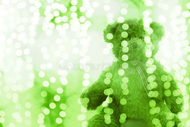De teddybeerpop in groene witte helder van de Verlichtingslijn bokeh voor Kerstmis of gelukkige nieuwe jaarachtergrond, draagt bi royalty-vrije stock fotografie