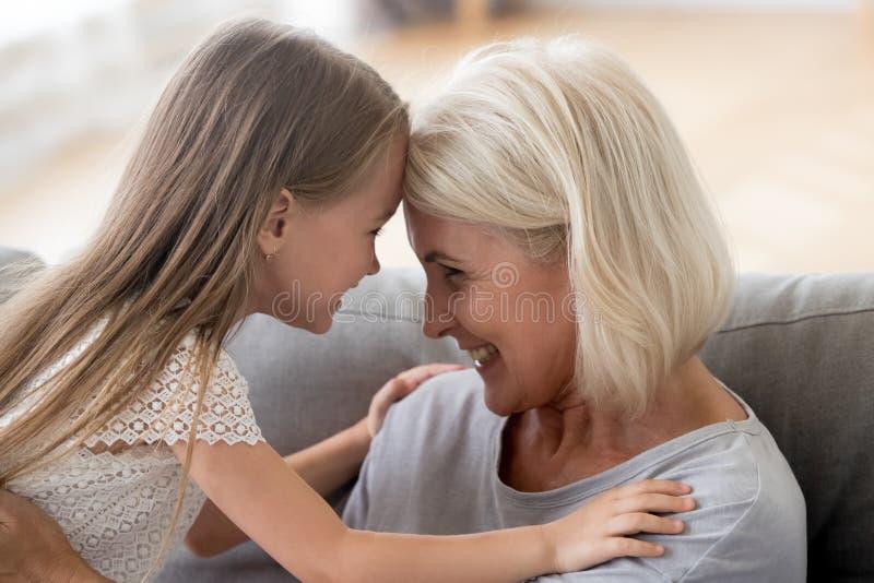 De tedere oma brengt tijd thuis met zoete kleindochter door stock fotografie