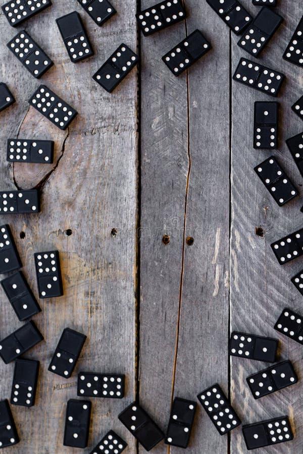 De tegels van de domino leiden tot een grens op een houten achtergrond stock foto
