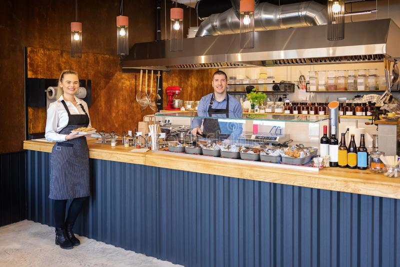 """De tegendienst bij moderne bistro met glimlachende kelners die voedsel†""""dienen gelukkige bedrijfseigenaars in klein restaurant  royalty-vrije stock afbeelding"""