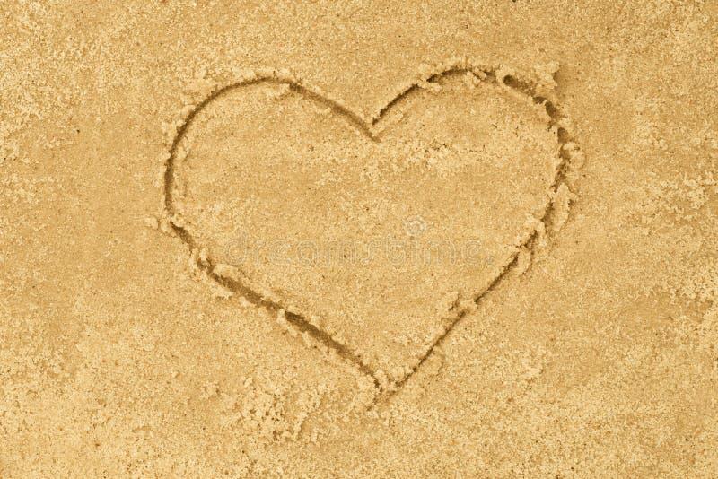 De tekening van de hartvorm in zand stock foto