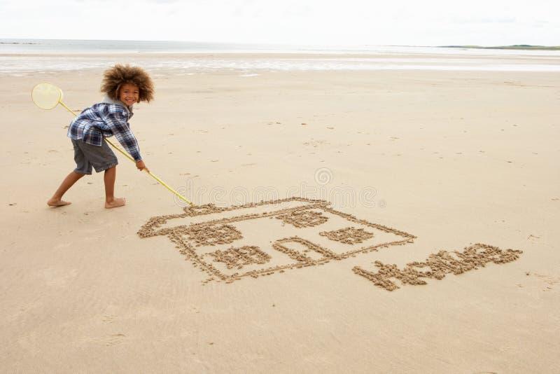 De tekening van de jongen in zand royalty-vrije stock afbeelding