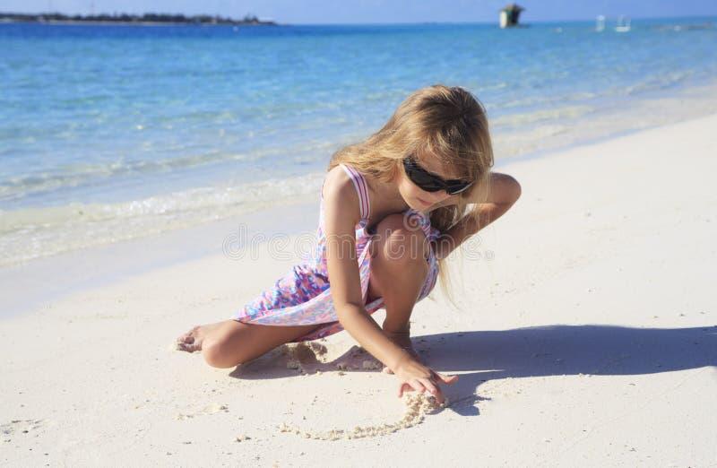 De tekening van het meisje in strandzand stock afbeelding