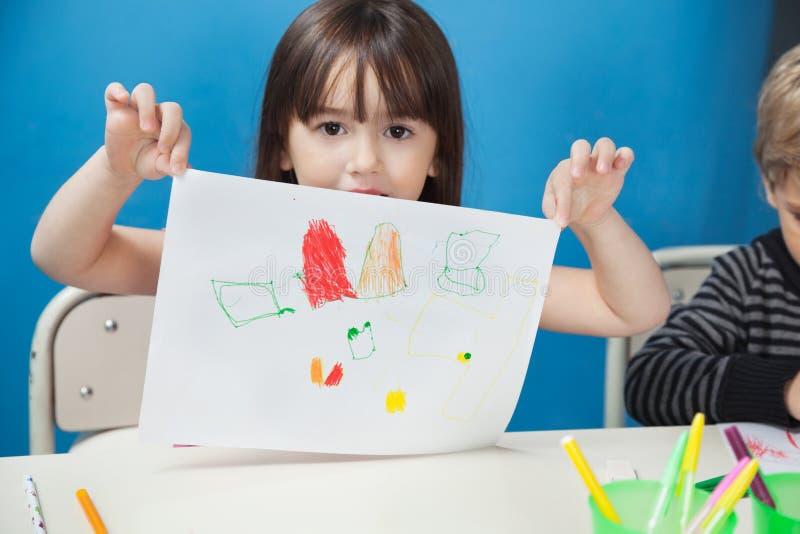 De Tekeningsdocument van de meisjesholding in Art Class royalty-vrije stock fotografie