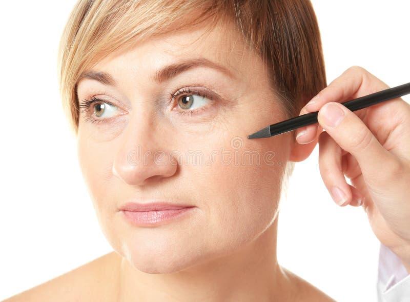 De tekeningstekens van de chirurgenhand op vrouwelijk gezicht voor verrichting royalty-vrije stock afbeelding