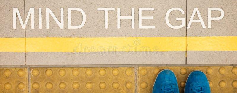 De tekenmening het hiaat schilderde op het platformrand van het station stock fotografie