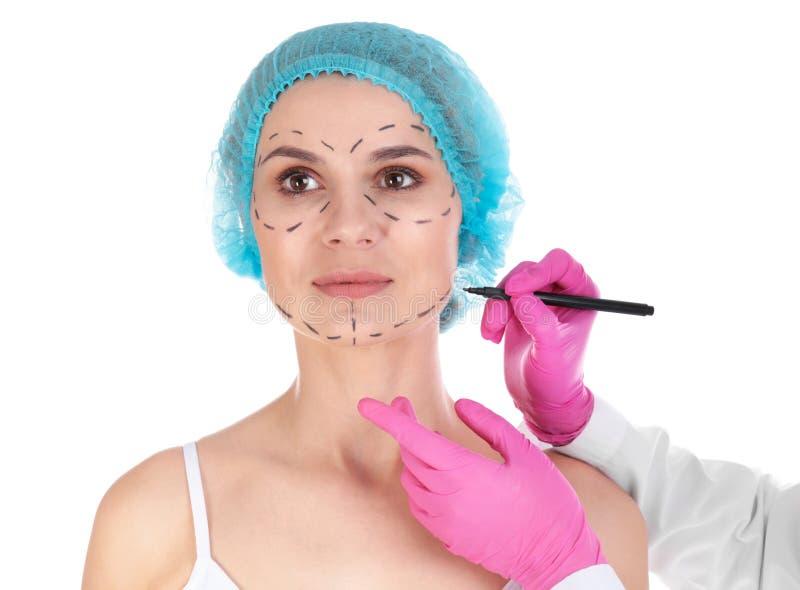 De tekens van de artsentekening op het gezicht van de vrouw tegen witte achtergrond royalty-vrije stock fotografie