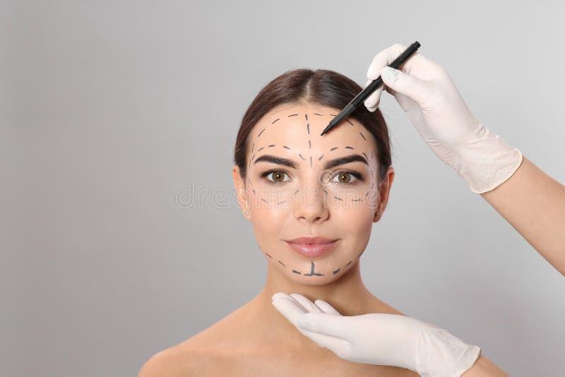 De tekens van de artsentekening op het gezicht van de vrouw voor kosmetische chirurgieverrichting stock fotografie
