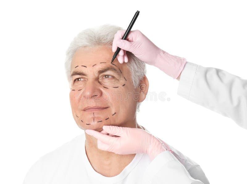 De tekens van de artsentekening op rijp man gezicht voor kosmetische chirurgieverrichting royalty-vrije stock fotografie