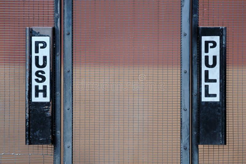De tekens van de duw en van de trekkracht op poort stock afbeeldingen