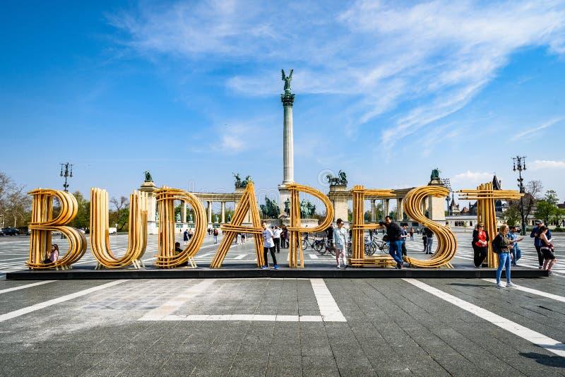 De tekst Boedapest maakte van hout op het Vierkant van Helden, Millenniummonument op de achtergrond stock foto's