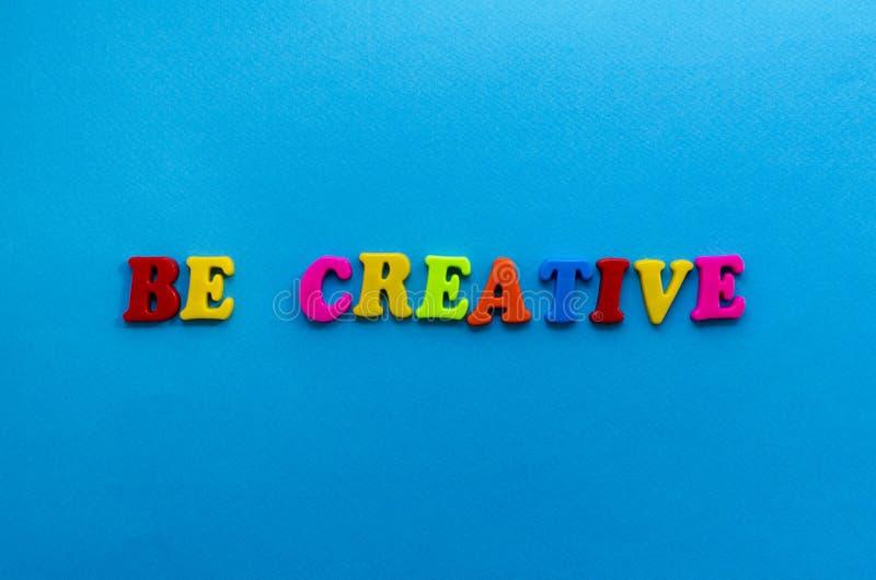 De tekst creatief is van plastiek kleurde brieven op blauwe document achtergrond stock afbeeldingen